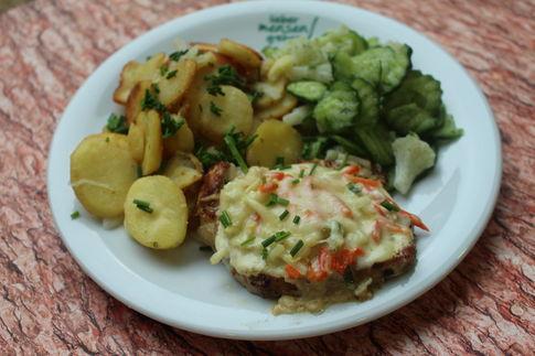 Rückensteak vom Schwein Berner Art (mit Gemüseauflage und Käse überbacken), dazu Bratkartoffeln und Gurken-Bohnensalat