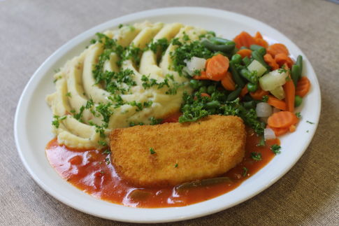 Vegetarisches Schnitzel mit Goudafüllung, dazu Paprikasoße, buntes Gemüse und Kartoffelpüree