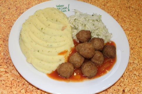 Köttbullar mit Paprikasoße, dazu Kartoffelpüree und Weißkohlsalat