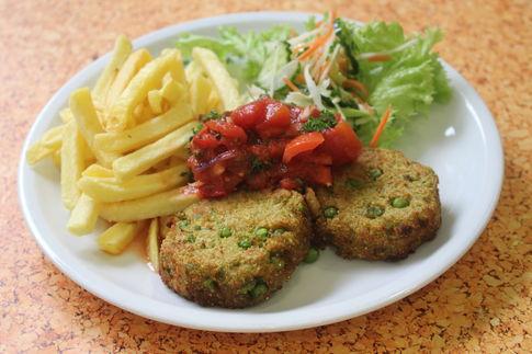 Zwei Erbsen-Quinoamedaillons mit Chili Tomaten Dip, dazu Pommes frites und Salatgarnitur