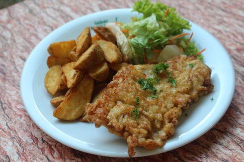 Putensteak in Käse-Eihülle, dazu Country-Kartoffeln und Salatgarnitur