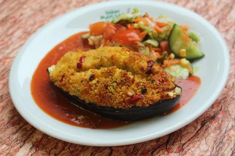 Gebackene Aubergine gefüllt mit Couscous, Gemüse und Hirtenkäse, dazu Tomatensoße und ein bunter Eisbergsalat