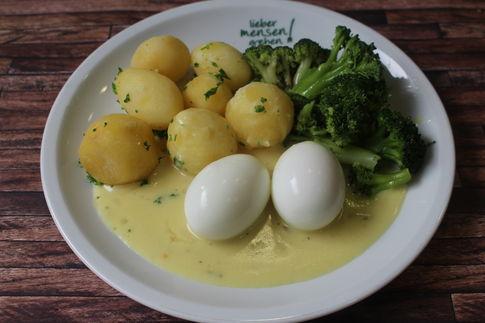 Zwei gekochte Eier in Senfsoße, dazu Broccoli und Petersilienkartoffeln