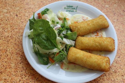 Drei Kartoffeltaschen mit Tomaten-Mozzarellafüllung auf einer Gemüsesoße, dazu ein bunter Salat