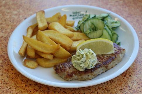 Steak vom Schweinerücken mit Kräuterbutter, dazu Steak fries und Gurkensalat