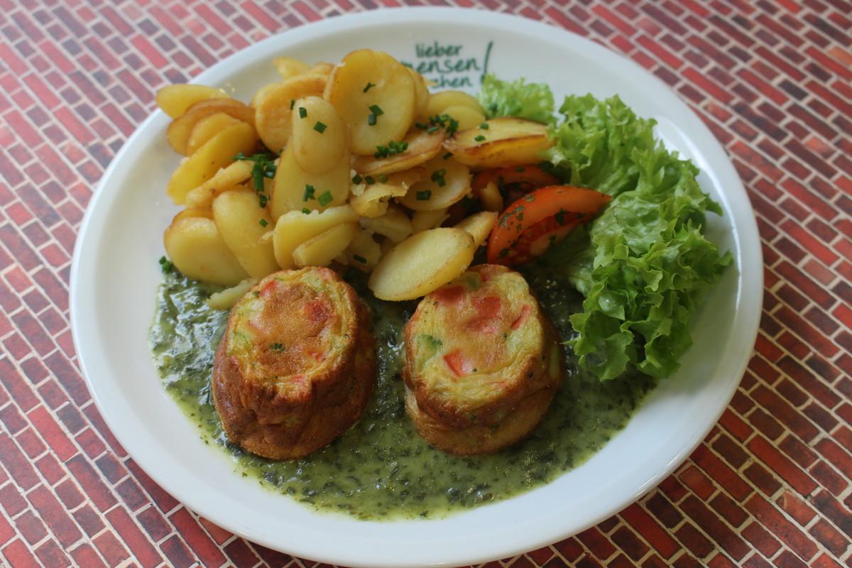 Zwei Mini Souffles mit Broccoli und Möhren auf einer Spinatsoße, dazu Bratkartoffeln und Salatgarnitur