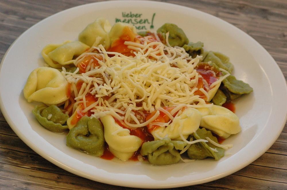 Bunte Tortelloni oder Vollkornspirelli in Tomatensoße, dazu geriebenen Gouda