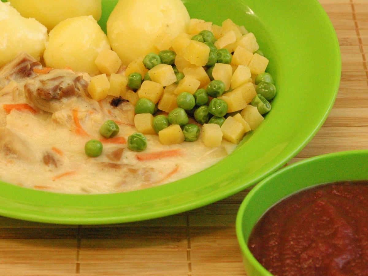 Geflügelfrikassee mit buntem Gemüse und Salzkartoffeln, dazu Fruchtmus (Cassis Johannisbeer)