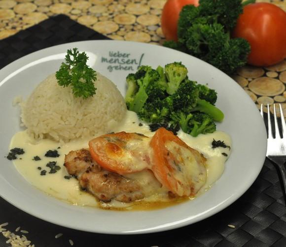 Mit Tomate und Mozzarella gratiniertes Hähnchenbrustfilet auf Basilikumsoße , dazu Broccoligemüse und Reis