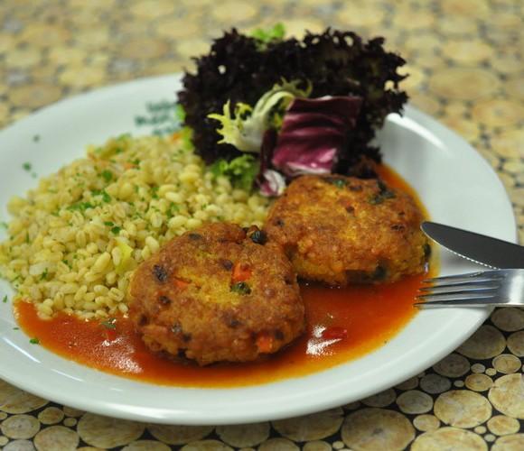 Türkische Linsenlaibchen auf Paprikasoße, dazu Gemüseebly und bunter Blattsalat