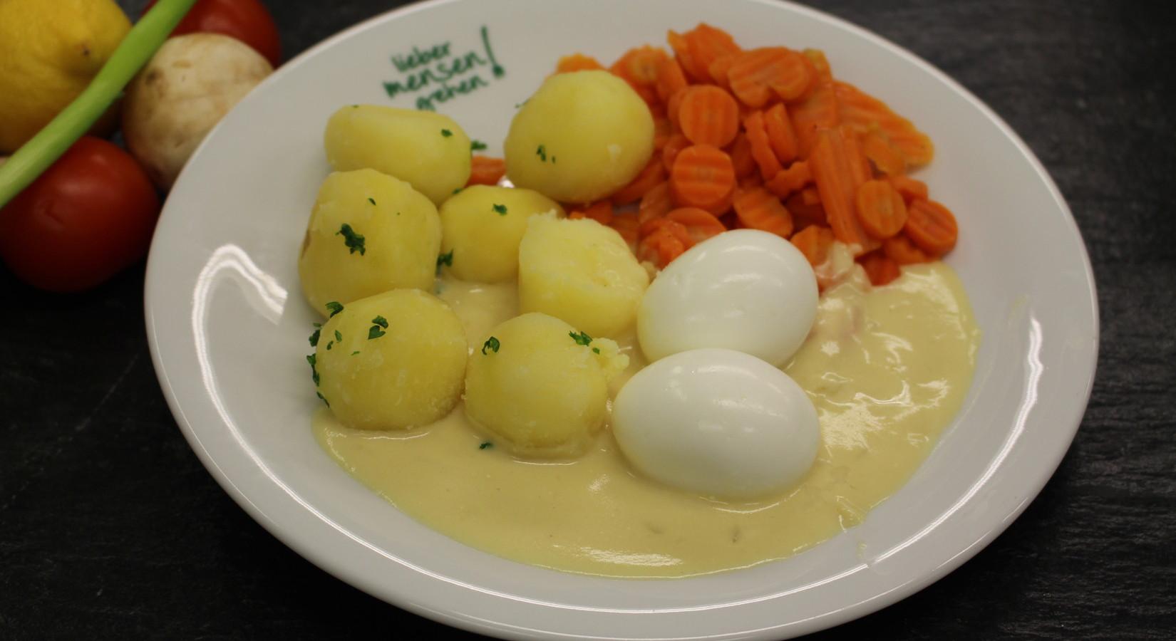 Zwei gekochte Eier auf Senfsoße mit Möhrengemüse und Petersilienkartoffeln